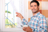 Man with bowl looking out the window — Stock Photo