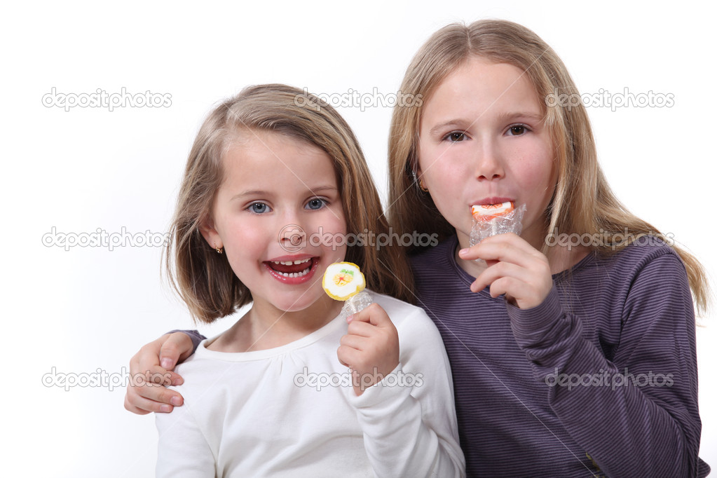 Two sisters eating lollipops. — Stock Photo #11031376
