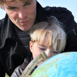 Father and son examining globe — Stock Photo #11041104