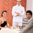 Chef stood with couple in restaurant - Stok fotoğraf