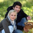 Couple with basket of mushrooms - Foto Stock