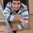 Foto Stock: Lad surrounded by cardboard boxes