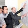 Architect checking plans stuck to office wall — Stock Photo #11044395