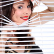 Sexy woman looking through the blinds — Stock Photo