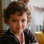 Little girl sat at the breakfast table — Stock Photo