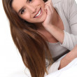Young woman smiling laid on a bed — Stock Photo #11047813