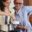 Stock Photo: Homecare cooking for senior woman