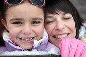 Mother and daughter giggling in the snow — Stock Photo