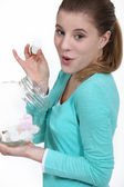 Cheeky woman eating marshmallow from jar — Stockfoto
