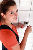 Tradeswoman fixing an electrical outlet — Stock Photo