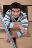 Lad surrounded by cardboard boxes — Stok fotoğraf