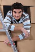 Rapaz, cercado por caixas de papelão — Foto Stock