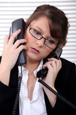 Overworked receptionist answering telephones — Stock Photo