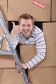 Factory worker emerging from cardboard boxes — Stock Photo
