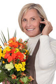 Mature florist holding bouquet — Stock Photo