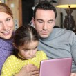 Parents and daughter sat with laptop on sofa — Stock Photo #11050007