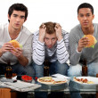 Boys eating burgers - Stock Photo