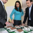 Couple with an architect looking at a housing model - Stock fotografie