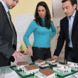 Couple with an architect looking at a housing model - Photo