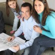 Family watching architectural blueprint — Stock Photo
