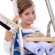Stock Photo: Little girl with step ladder and wallpaper
