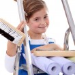 Little girl with step ladder and wallpaper - Stock Photo