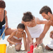 Stock Photo: Family making sandcastle