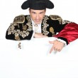 Man in a matador costume with a board blank for text or image — Stock Photo #11054567
