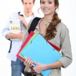 Two students carrying paperwork — Stock Photo