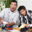 Father and son having fun playing video games — Stock Photo