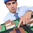 Stock Photo: Architect pointing to solar panel on model house