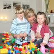 Happy grandmother playing legos with grandchildren - Stock Photo