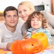 Family carving a pumpkin together — Stock Photo #11057175