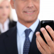Man using a cellphone with his assistant in the background — Stock Photo