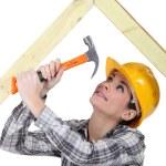 Tradeswoman hammering a frame — Stock Photo #11057902