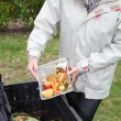 Stock Photo: Wommaking compost from old vegetables