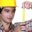 Foto Stock: Builder holding tape measure
