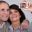 Middle aged couple taking a picture of themselves - Stock Photo