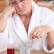 Elderly lady sat with her medication — Stock Photo