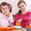 Girls squeezing oranges — Stock Photo