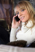 Woman in cosy jumper sat on couch making telephone call — Stock Photo