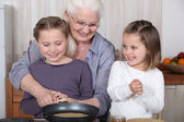 Sisters cooking pancakes with grandmother — Stock Photo
