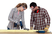 Couple drilling wood — Stock Photo