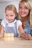 Woman and child playing dominoes — Stock Photo