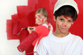 Children painting a room red — Stock Photo