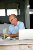 Senior man trying to sort hiss house bills out — Stock Photo