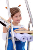 Little girl with step ladder and wallpaper — Stock Photo
