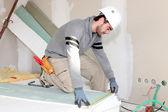 Bricklayer measuring plasterboard — Stock Photo