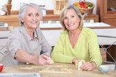 Duo of retired ladies playing scrabble in the kitchen — Stock Photo