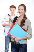 Two students carrying paperwork — Foto Stock